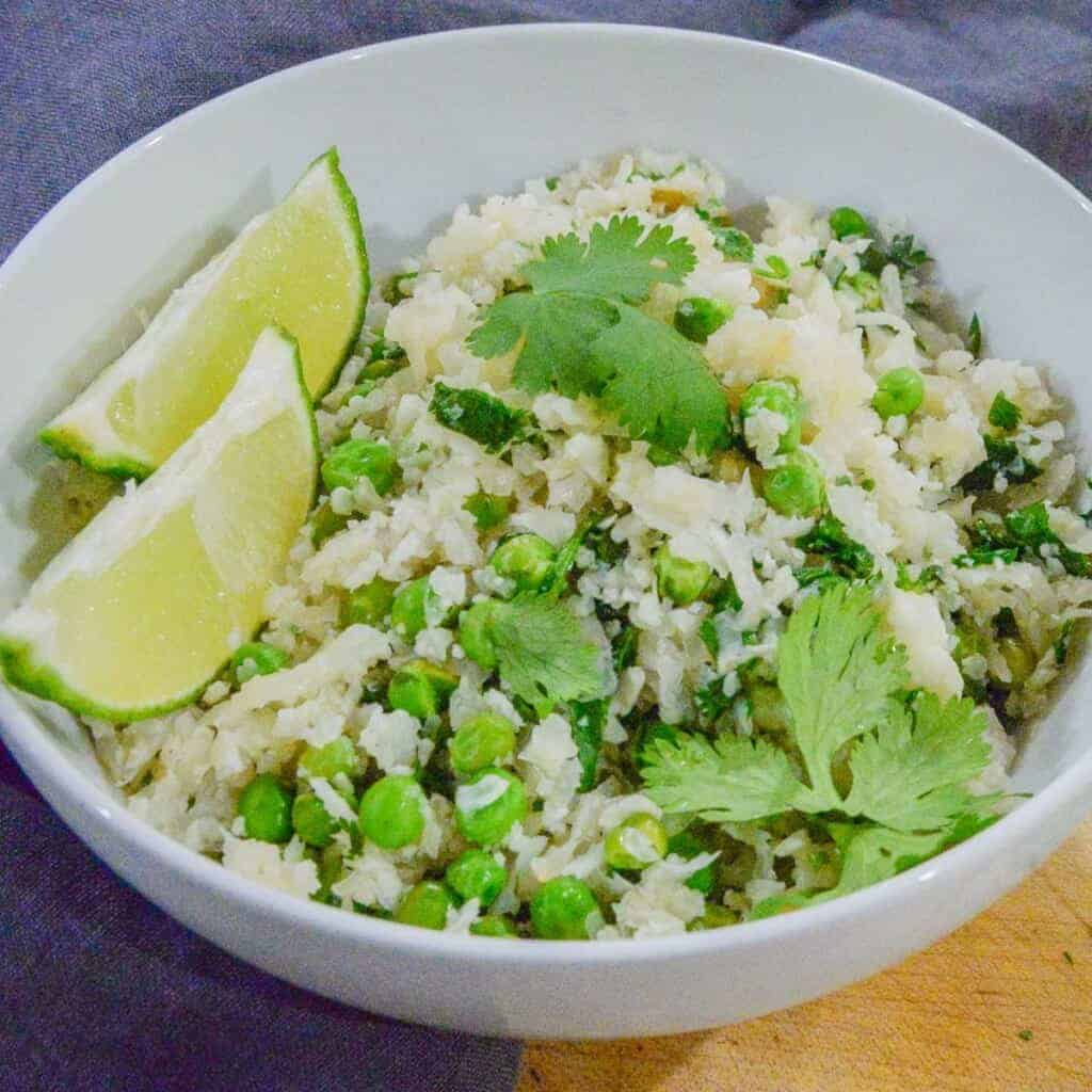 Cilantro Lime Cauliflower Rice in a white bowl, served with lime.