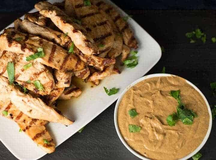 plate of grilled chicken satay tenderloins served with creamy peanut sauce.