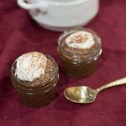 two dark Chocolate Pots de Crème topped with creme fraiche and chocolate shavings.