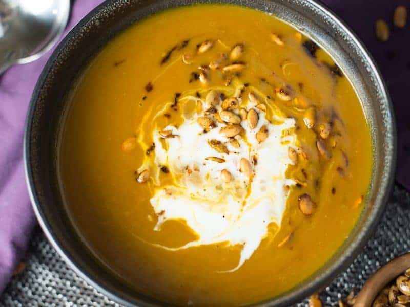 A black bowl filled with pumpkin spice soup. Topped with crunchy toasted pepitas and creme fraiche.