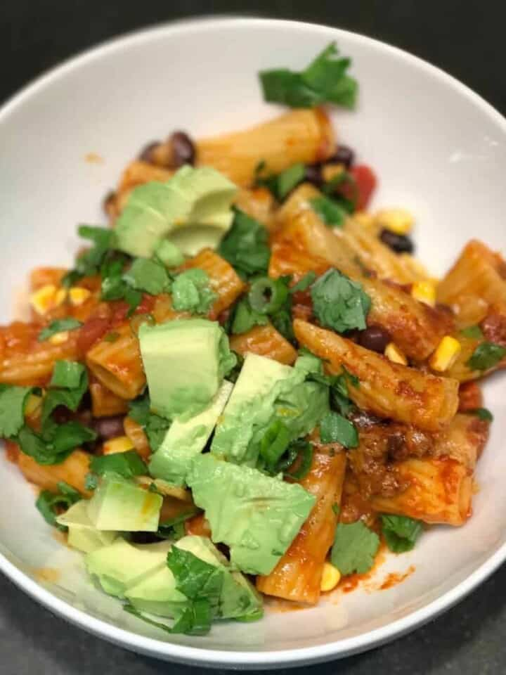 Bowl full of enchilada pasta casserole topped with fresh avocado, green onions, and cilantro. recipe by foodology geek.