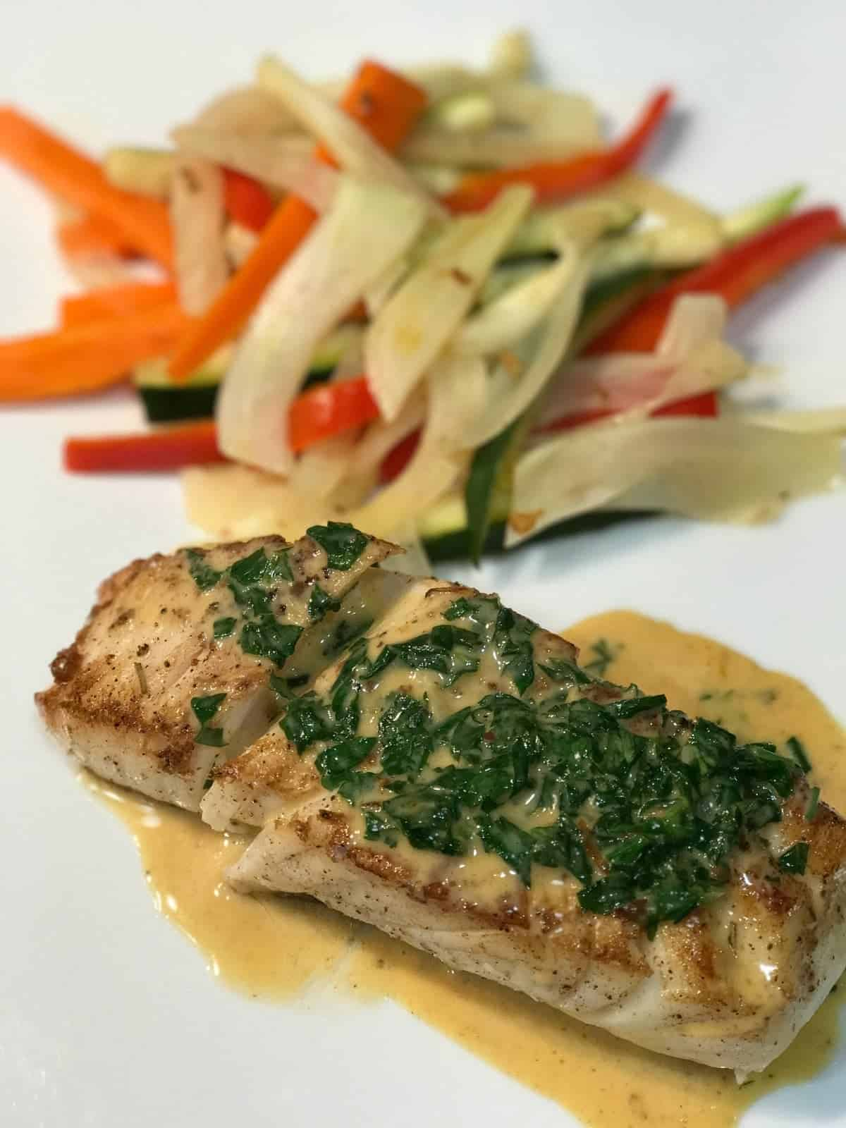 Pan Seared Halibut with Citrus Cream Sauce served with juleinned fennel, carrots, zucchini, and red peppers. Recipe by foodology geek.