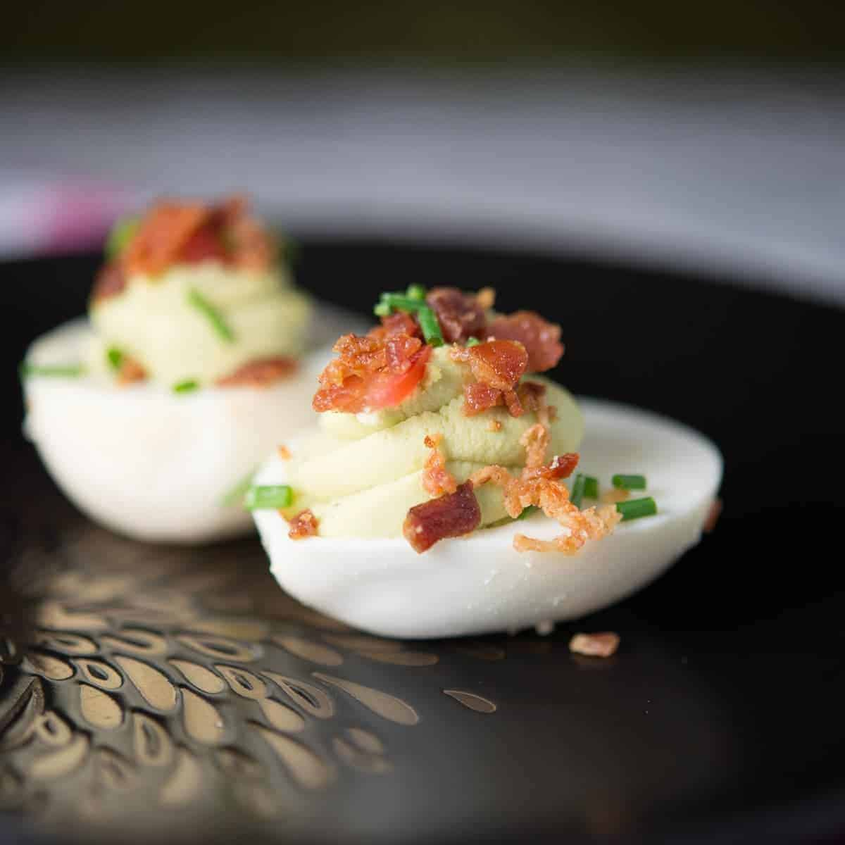 fancy deviled eggs filled with avocado and topped with bacon and chives. recipe by foodology geek