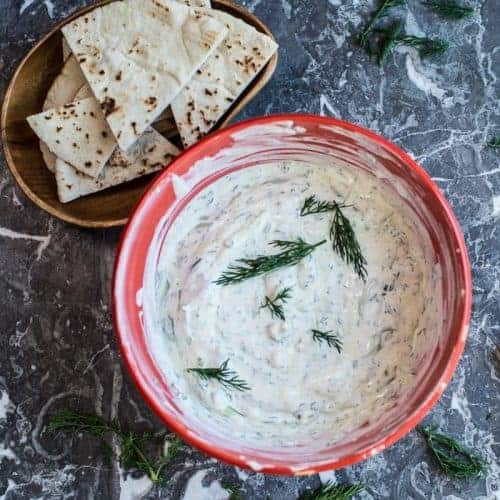 a bowl of fresh cucumber sauce with fresh pita bread. by foodology geek.