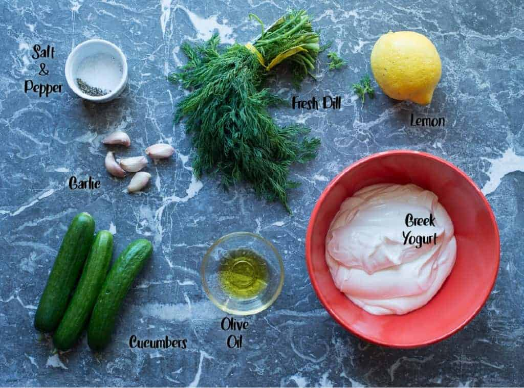 Tzatziki Ingredients on a marble board: yogurt, cucumber, dill, olive oil, lemon and garlic by foodology geek.