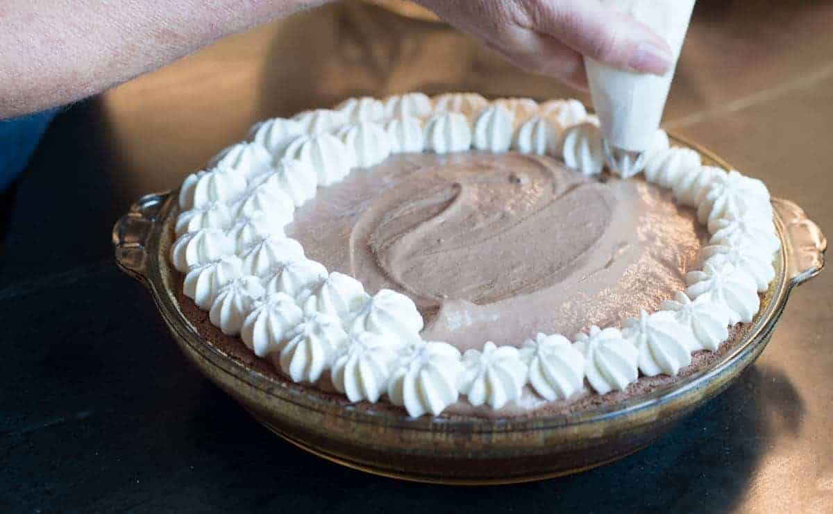 Piping whipped cream on chocolate pie