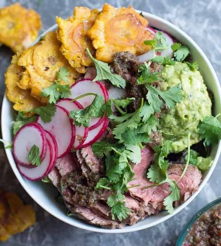 Steak salad with chimichurri sauce, guacamole, and tostones. by foodology geek