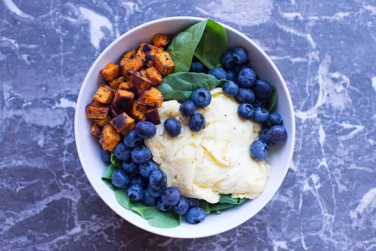 Paleo Breakfast Bowl Recipe with eggs, blueberries, spinach, and roasted sweet potatoes.