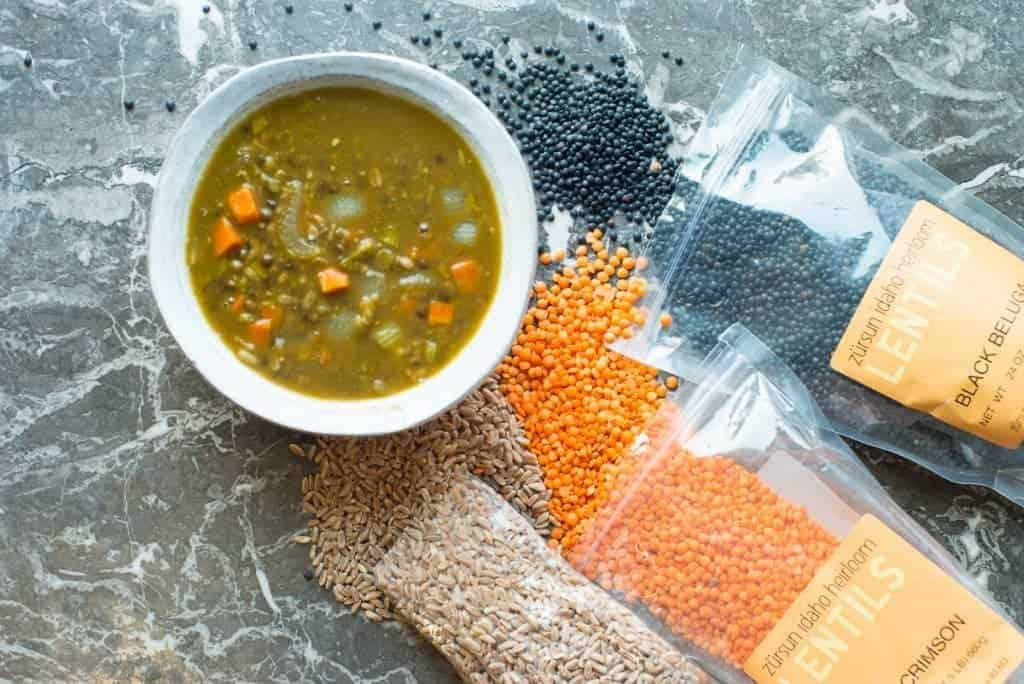 Lentil vegetable soup recipe in a bowl. Surrounded by black belug lentils, red lentils, and farro by foodology geek.