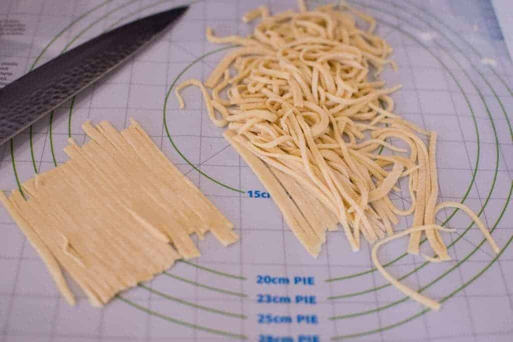 Hand cut drop noodles on a cutting board.