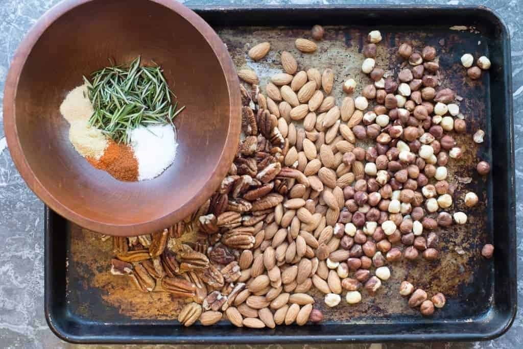 Spiced nuts recipe. Pecans, almonds and hazelnut on a baking sheet with mixed spices and fresh rosemary. by foodology geek
