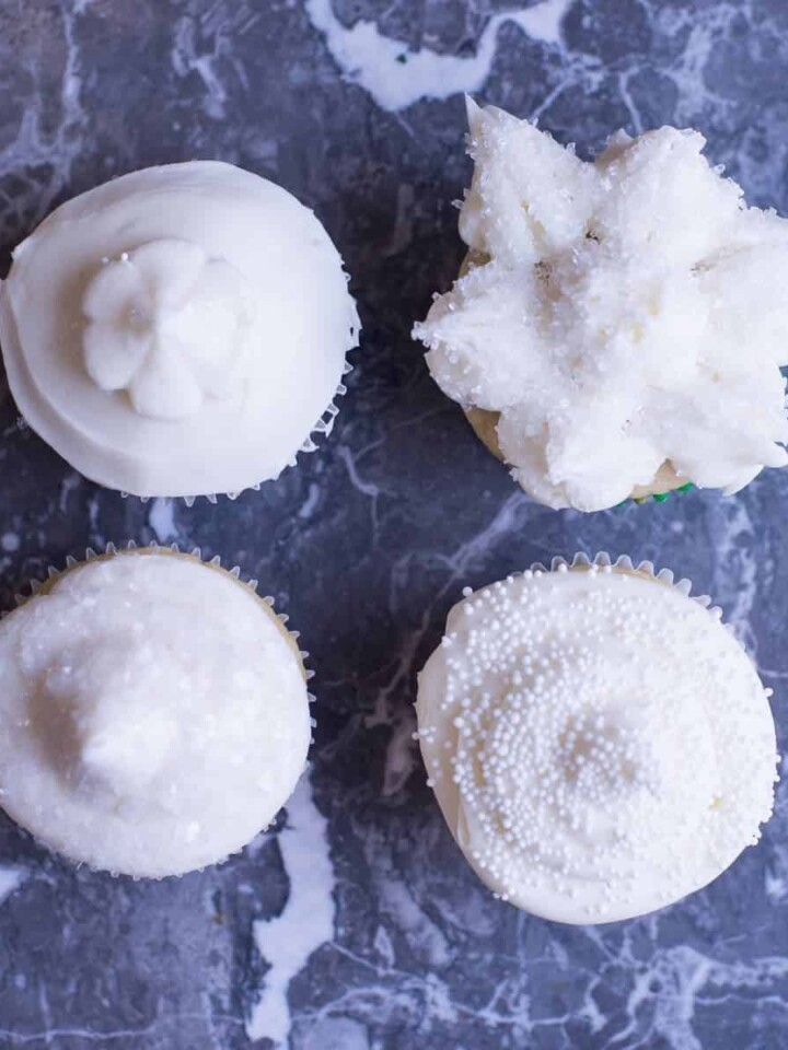 simple vanilla cupcakes decorated with buttercream frosting and white sprinkles.