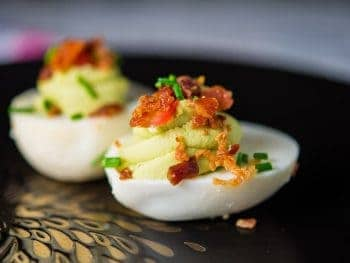 Avocado deviled eggs with crispy bacon, fresh tomatoes and chives.
