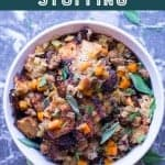 Thanksgiving stuffing made with sausage, apples, and sourdough bread. Baked in a white casserole dish. Pinterest image by foodology geek.