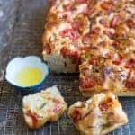 Foccacia with tomatoes, garlic and rosemary served with olive oil.