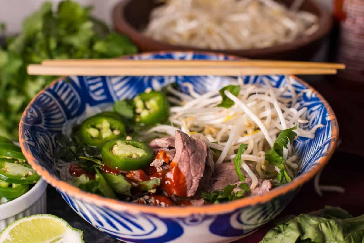 Bowl of Pho with Sriracha and chopsticks