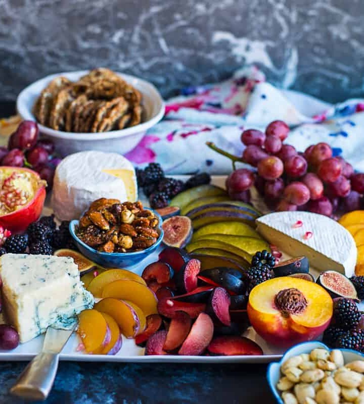 gourmet cheese board with stone fruit, pomegranate, roasted nuts, blue cheese, brie, and dried fruits.