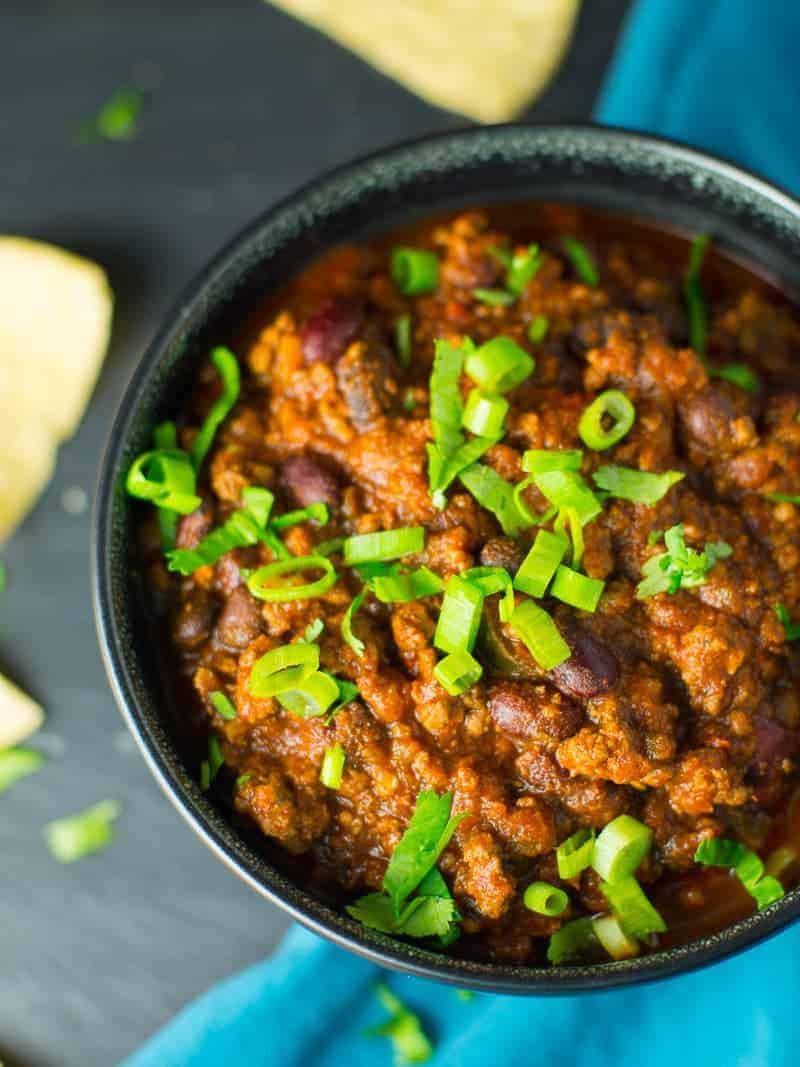 Ground beef and bean chili recipe. Sprinkled with green onions. Served with tortilla chips.