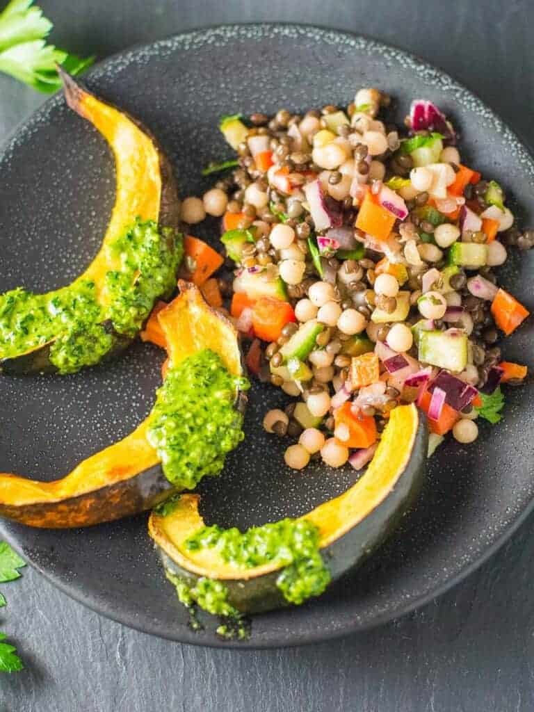 cous cous salad served with roasted acorn squash and kale pesto