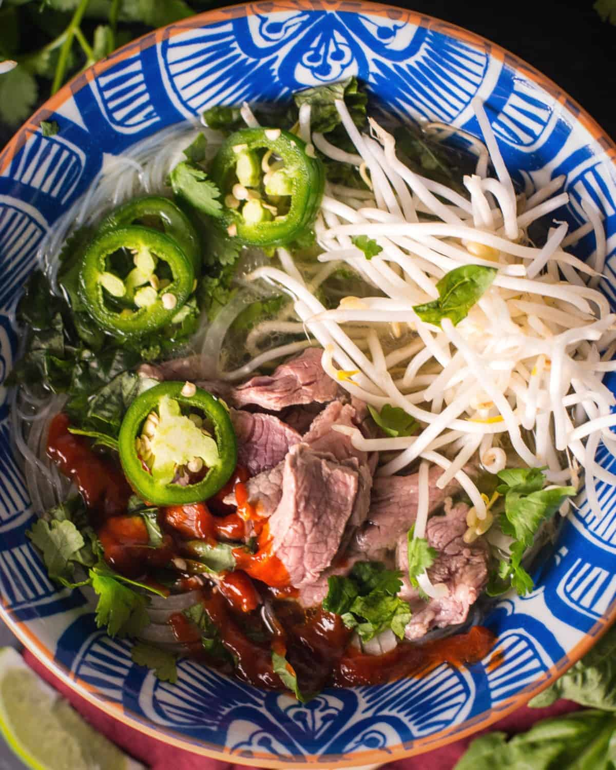 pho tai served in a large bowl with bean sprouts, jalapenos, and plenty of sriracha