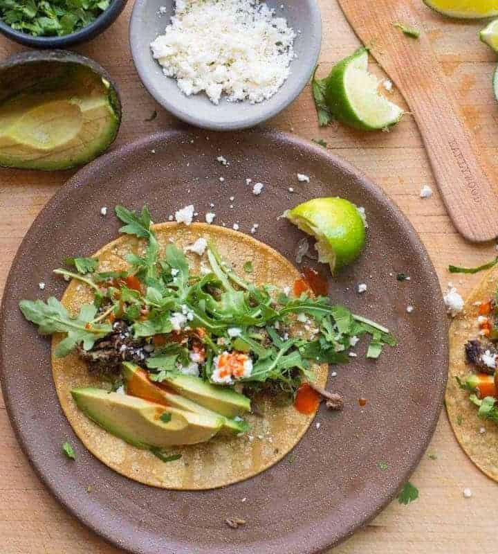 Shredded beef tacos with sliced avocado, cotija cheese, tapatio and limes. recipe by foodology geek