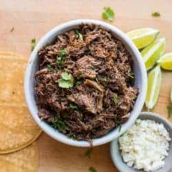 Easy slow cooker mexican shredded beef recipe with tortillas, limes, and cotija cheeses.