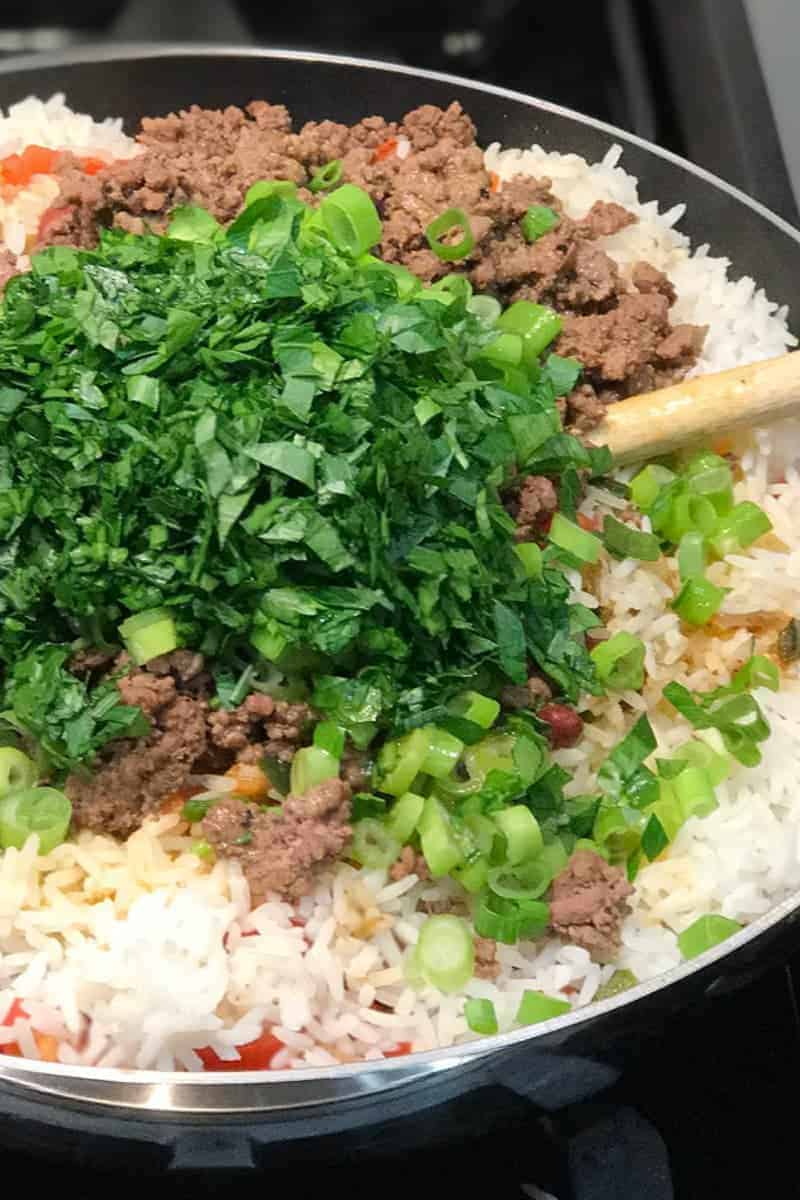 Making Puerto Rican Dirty Rice - add ground beef and fresh veggies, then toss well until combined.