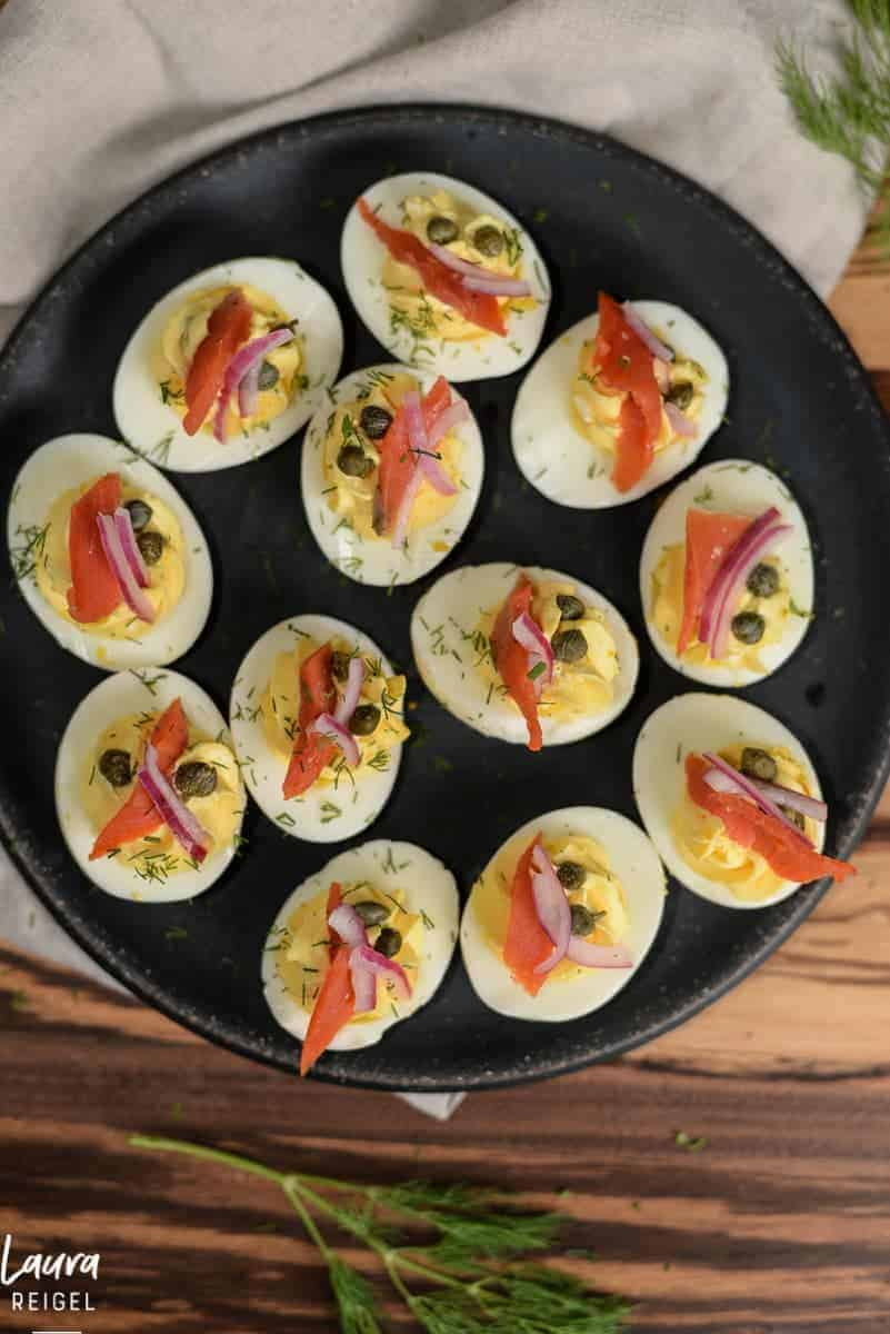 plate of deviled eggs topped with smoked salmon, capers, and red onions. recipe by foodology geek.