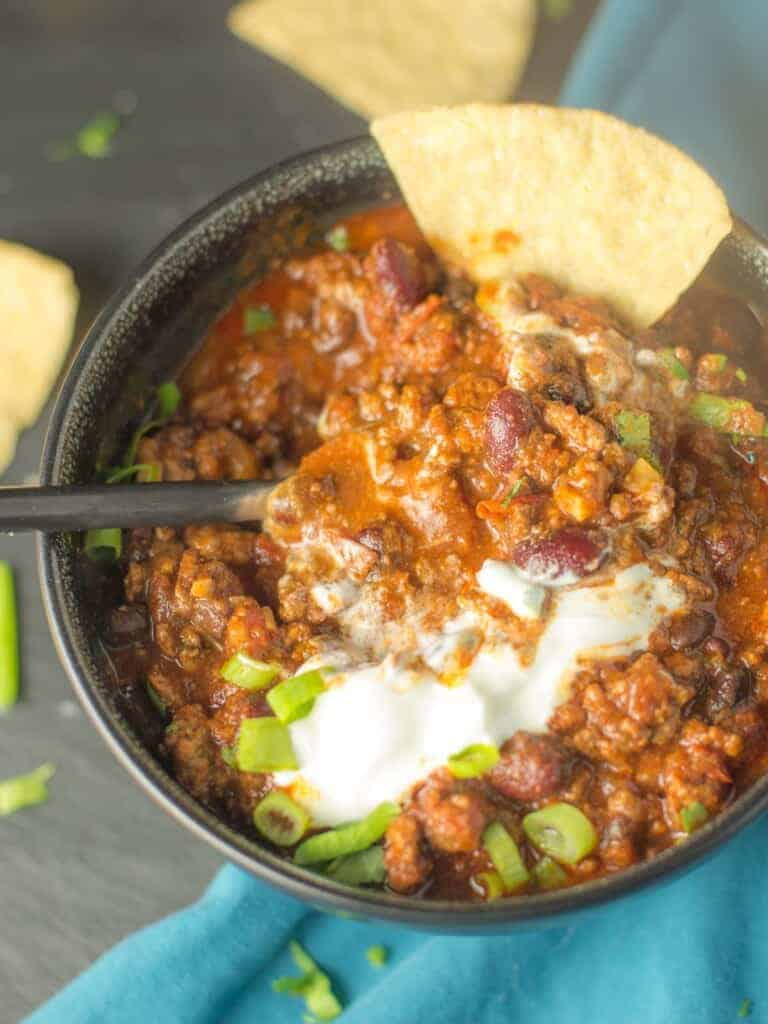hearty chili with sour cream, green onions, and tortilla chips