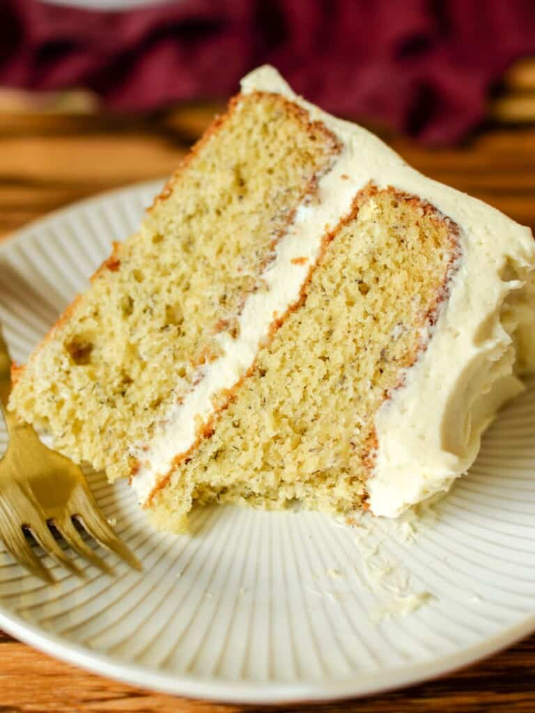 a slice of light and fluffy banana cake with cream cheese frosting