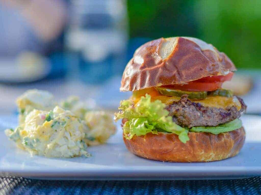 grilled burger served with classic creamy potato salad