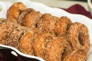 A dozen apple cider donuts covered in cinnamon sugar, in a black and white dish.
