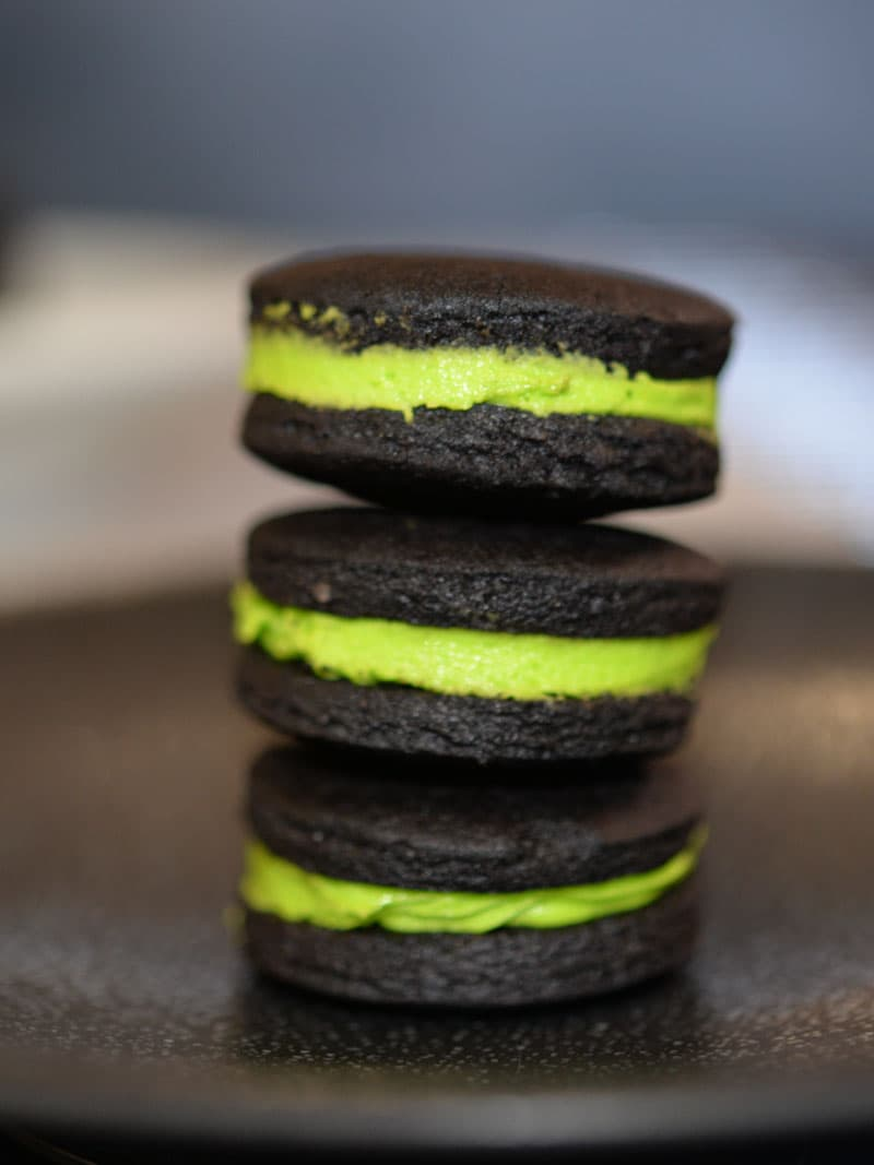 A stack of chocolate sandwich cookies, like oreos, filled with Frankenstein Green butter cream.