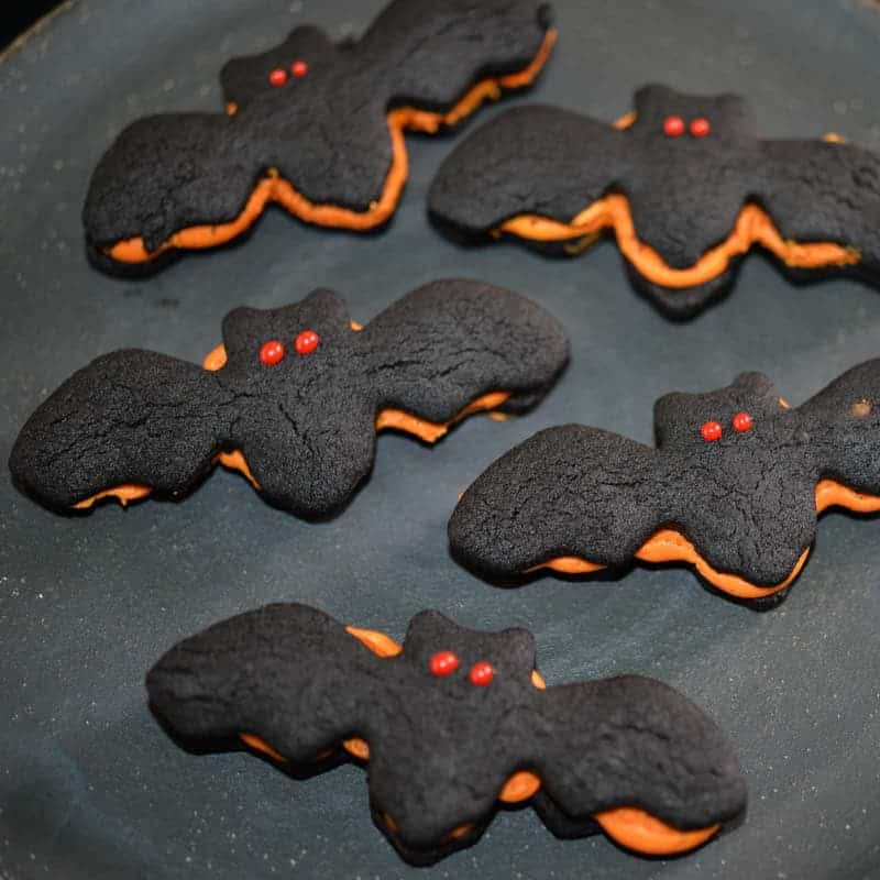 Bat Shaped dark chocolate sandwich cookies, filled with orange buttercream and decorated with red bat eyes.