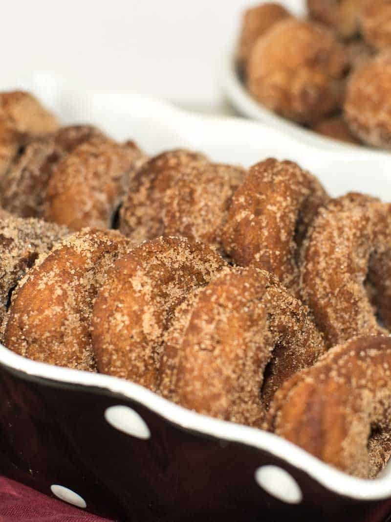 Homemade apple cider donuts dusted with cinnamon and sugar in a black and white polka dot dish.