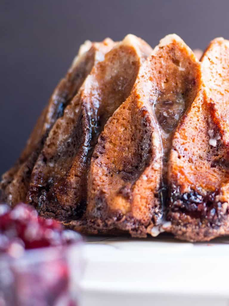 Cranberry and Cinnamon Sour Cream Coffee Cake with a Grand Marnier Glaze. Made in a bundt pan and set on a white cake pan.