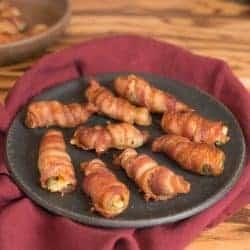 Bacon wrapped buffalo shrimp stuffed with brie on a black plate