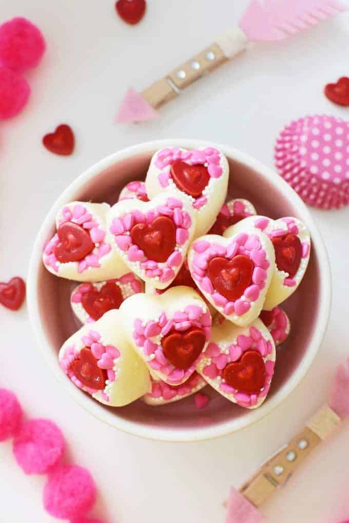A bowl of homemade white chocolate heart candies topped with pink and red heart shaped sprinkles.