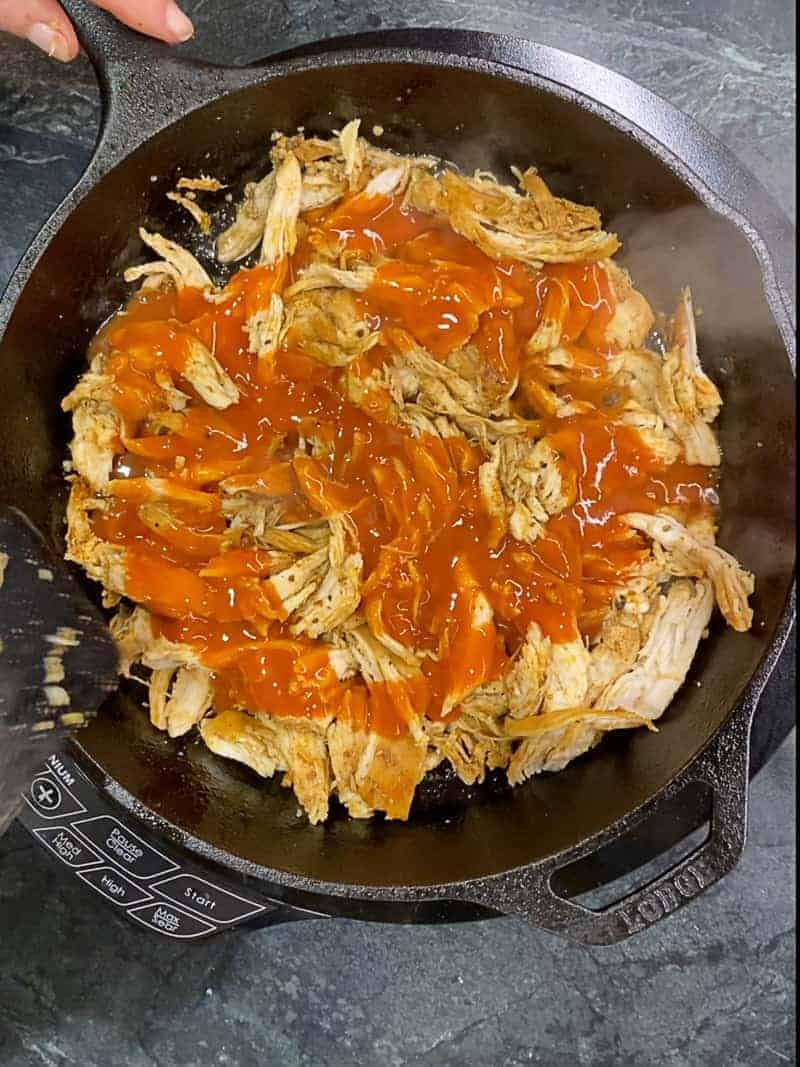 shredded chicken in a cast iron pan covered in franks red hot sauce.