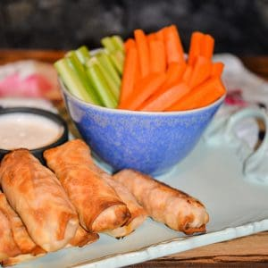 Buffalo Chicken Egg Rolls on a platter with celery and carrot sticks.
