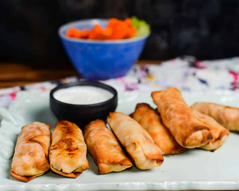 Buffalo chicken egg rolls served with blue cheese dressing and carrot and celery sticks.