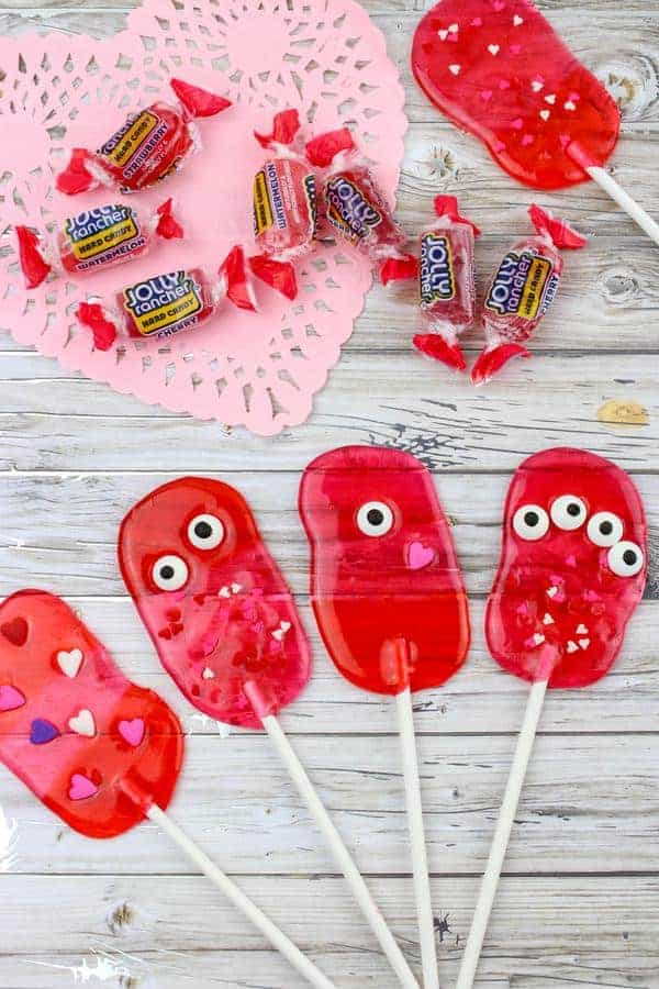 5 lollipops made from jolly rancher candies decorated with monster eyes and hearts.