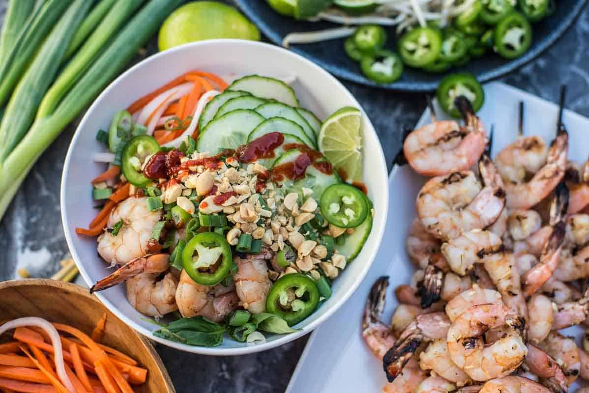 Vietnamese shrimp bowl recipe served with rice noodles, cucumbers, carrots, peanuts and sriracha by foodology geek.