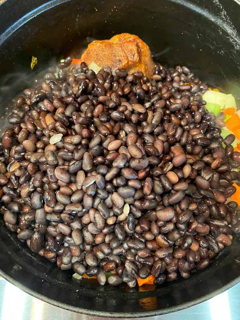 Add the presoaked black beans to the dutch oven or stock pot.