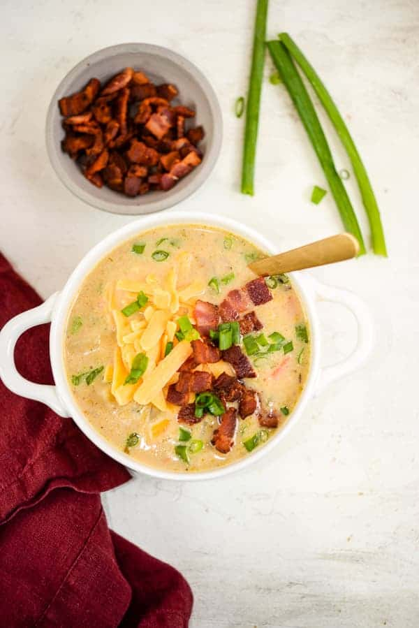 Bowl of homemade potato soup with bacon, cheese, and green onions.