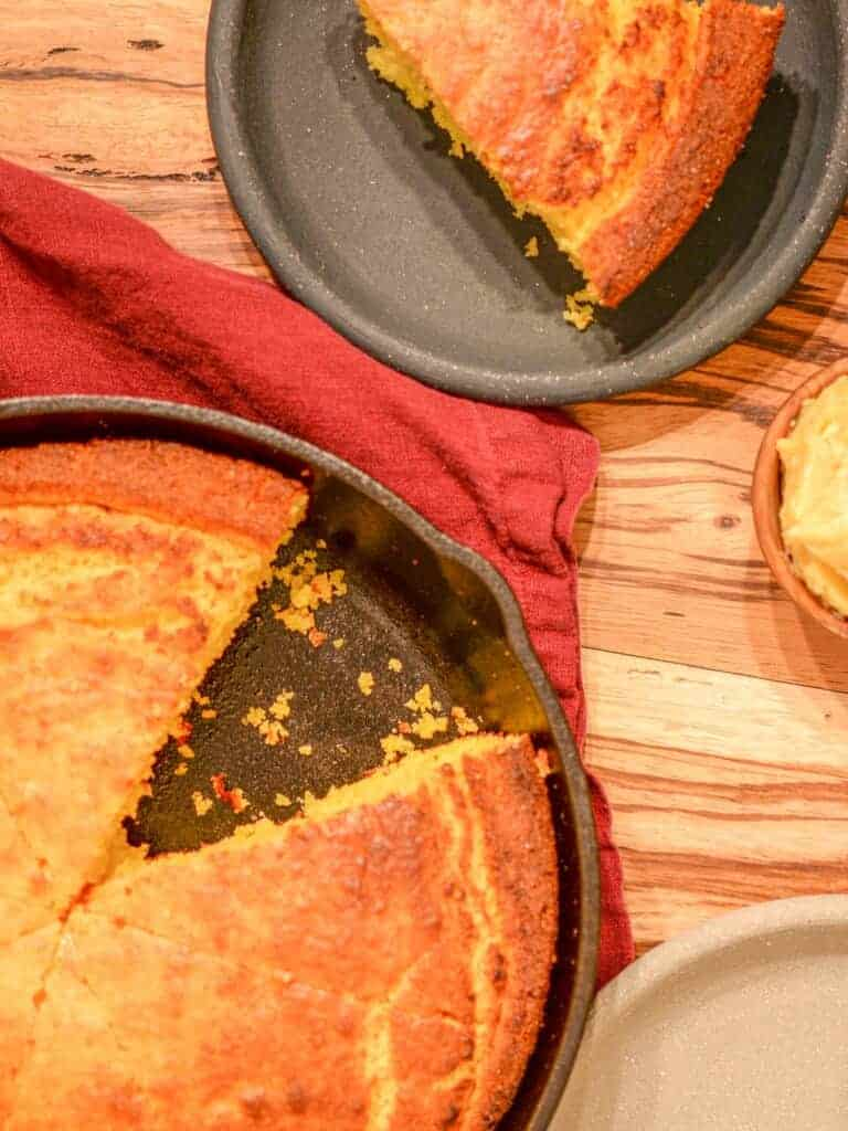 Buttermilk cornbread in a cast iron skillet with one slice cut out.
