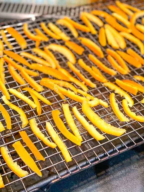orange peels drying on a wire rack after boiling in sugar syrup.