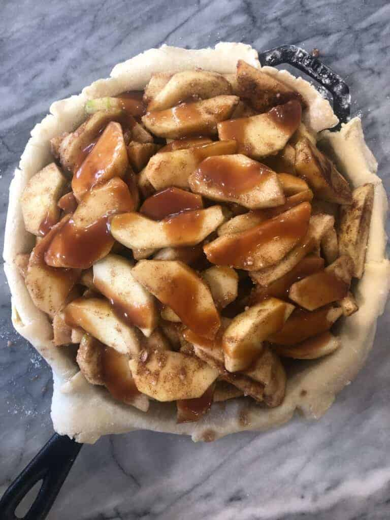 add the apples and the caramel to the pie dough