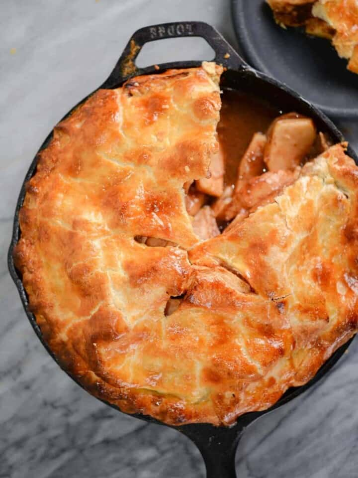 cast iron baked apple pie recipe with a slice cut out