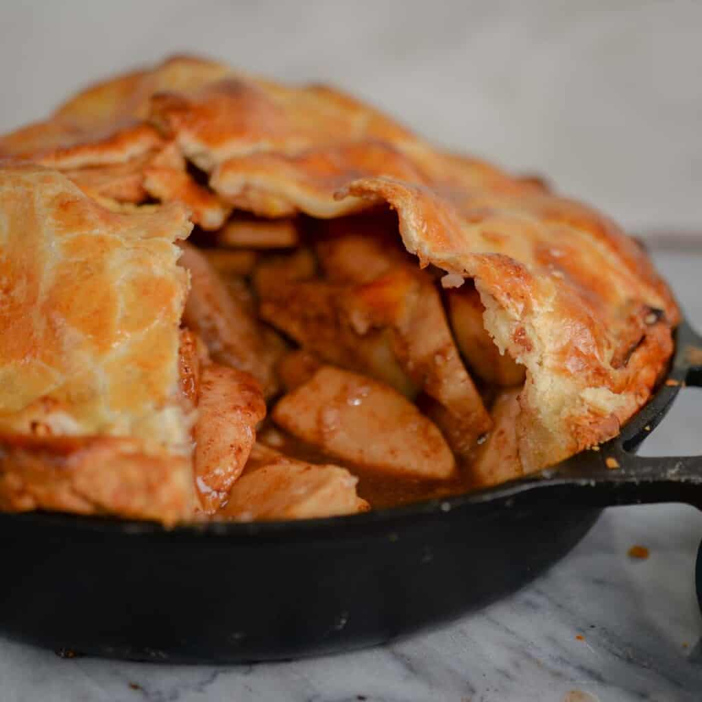 apple pie filling with caramel sauce baked in a cast iron skillet